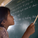 "A student of Khmer descent learns Kinh language (the official Vietnamese language) at the Lac Hoa Primary School in Soc Trang province. The report ""Vietnam High Education For All by 2020"" finds that gaps in learning still exist, particularly between groups of different income levels and between Kinh, Chinese and ethnic minorities. Soc Trang province, Vietnam. Photo: Chau Doan / World Bank"